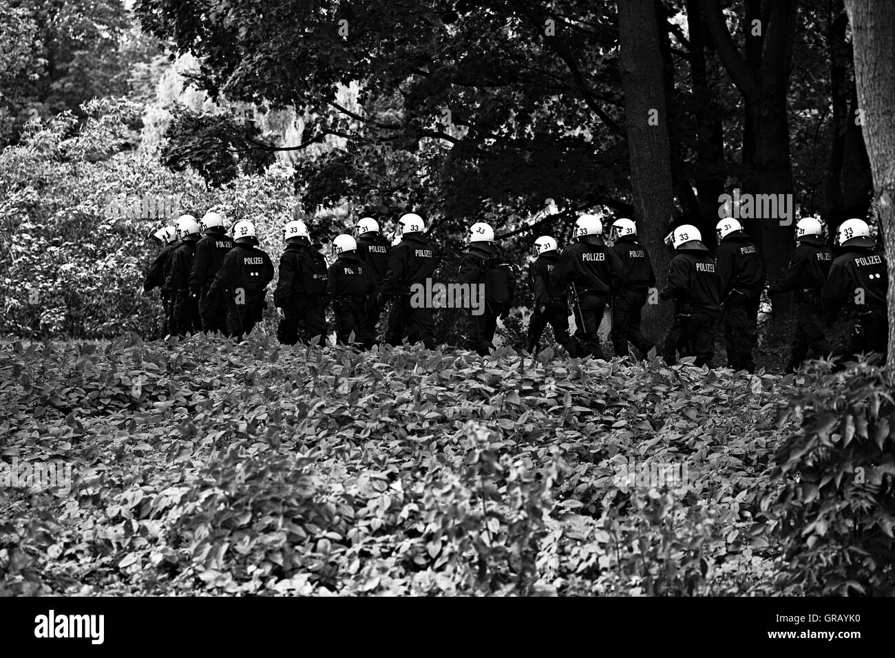 Police Force Walking By Plants And Trees - Stock Image