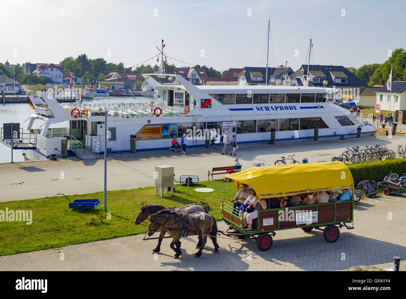 Harbor In Vitte With Ferry To Schaprode And Yellow Covered Horse-Drawn Caravan - Stock Image