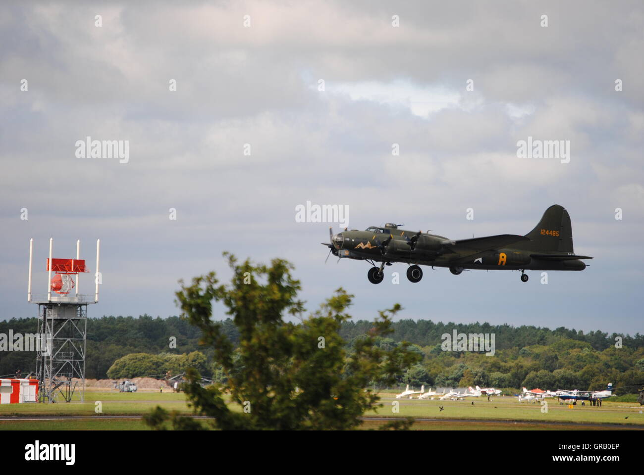 Military Airplane Flying Over Landscape Against Cloudy Sky - Stock Image