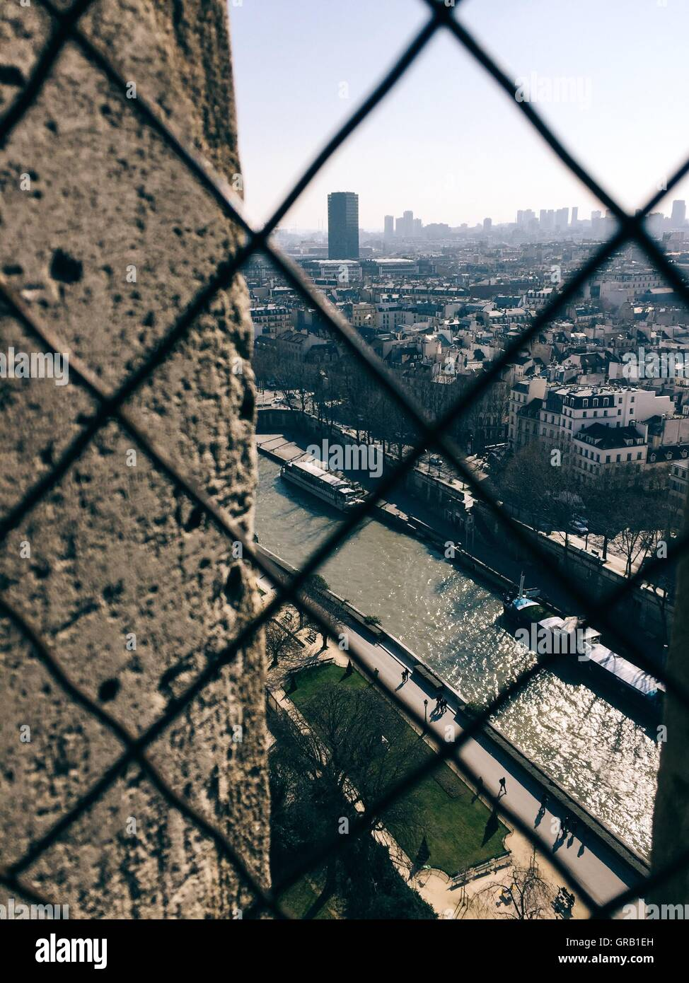 Seine River Amidst Cityscape Against Sky Seen Through Chainlink Fence - Stock Image