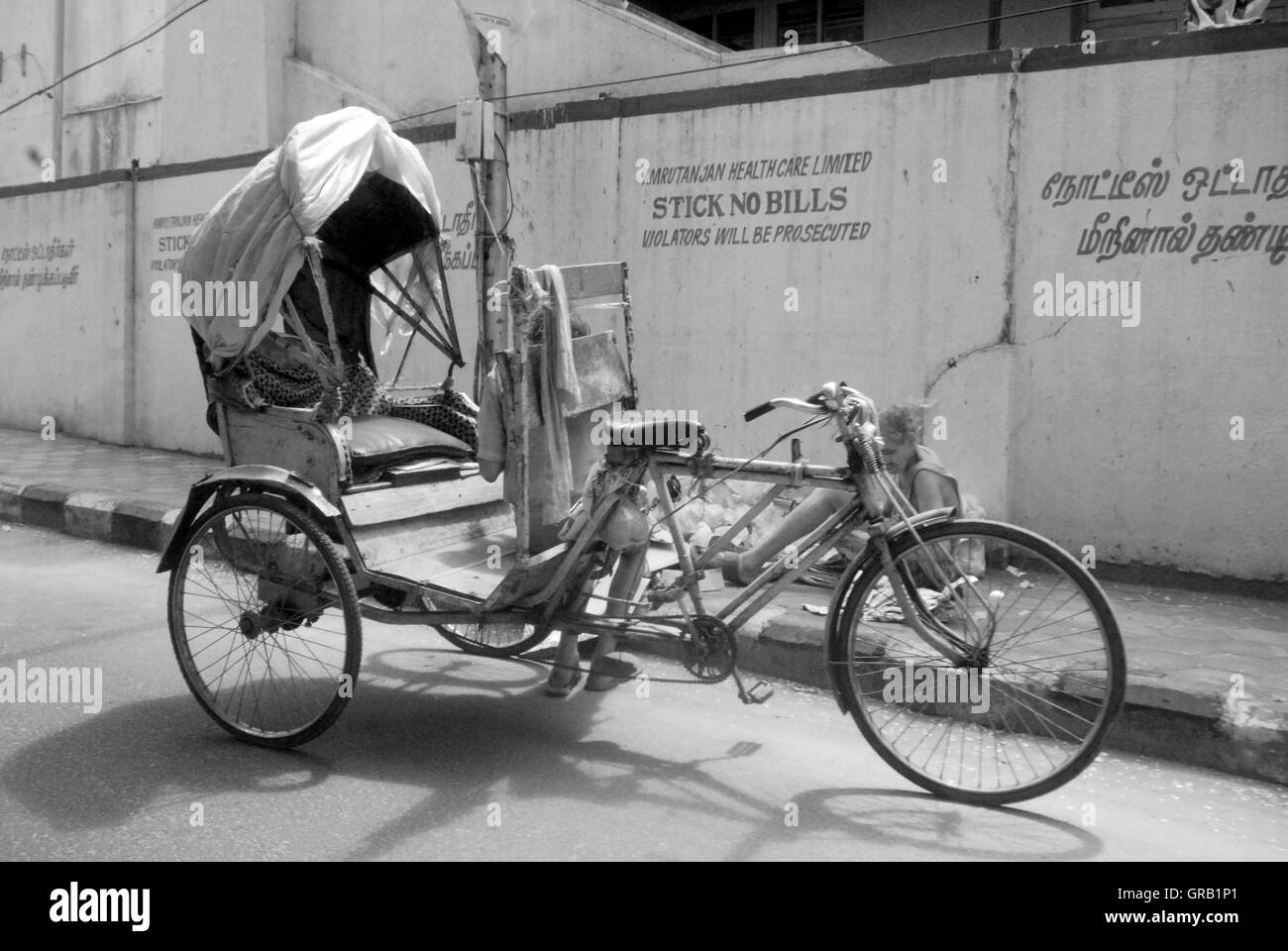 Tricycle Parked On Street Against Building During Sunny Day - Stock Image