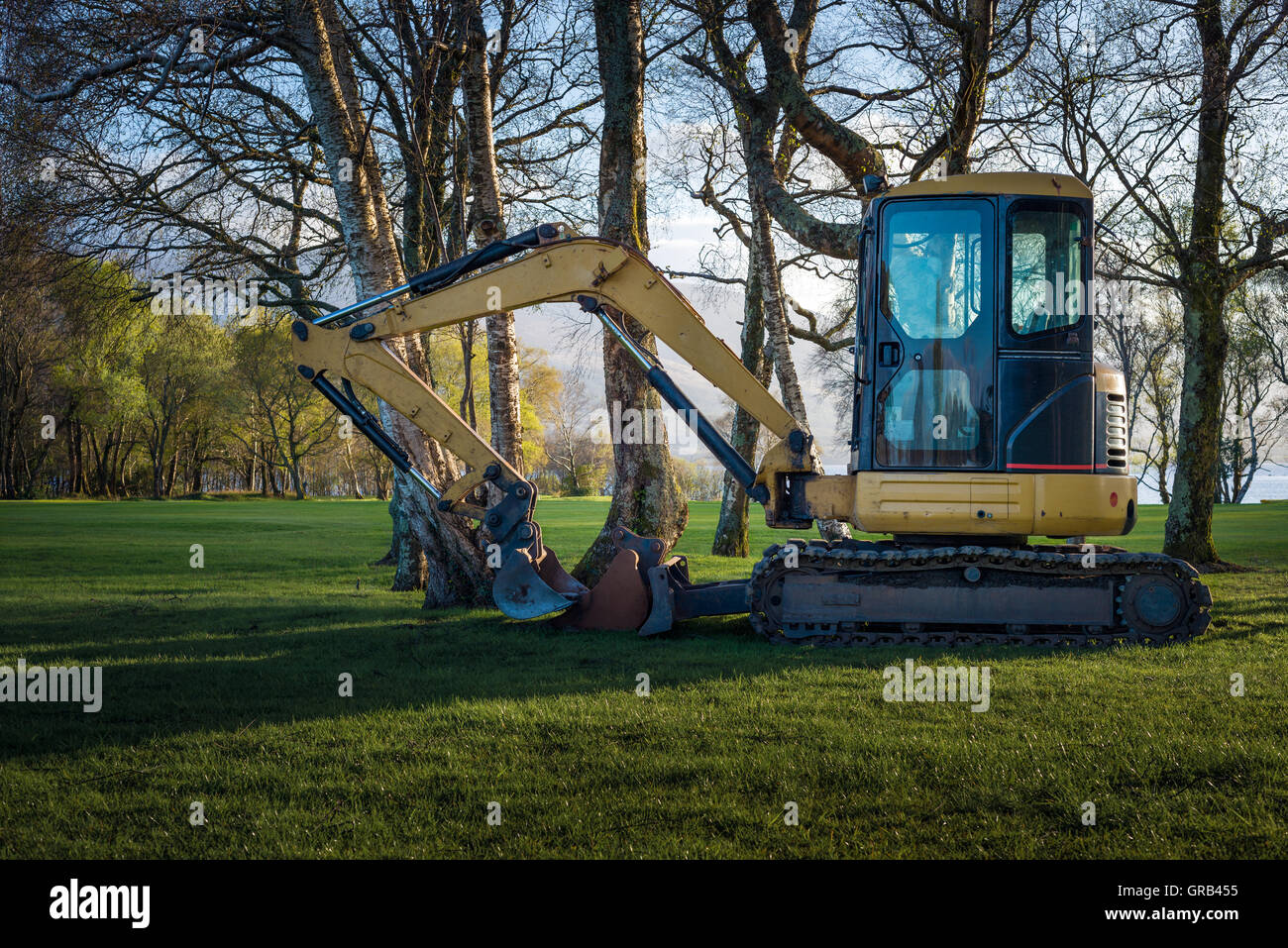 Bagger at a golf course among trees at sunset - Stock Image