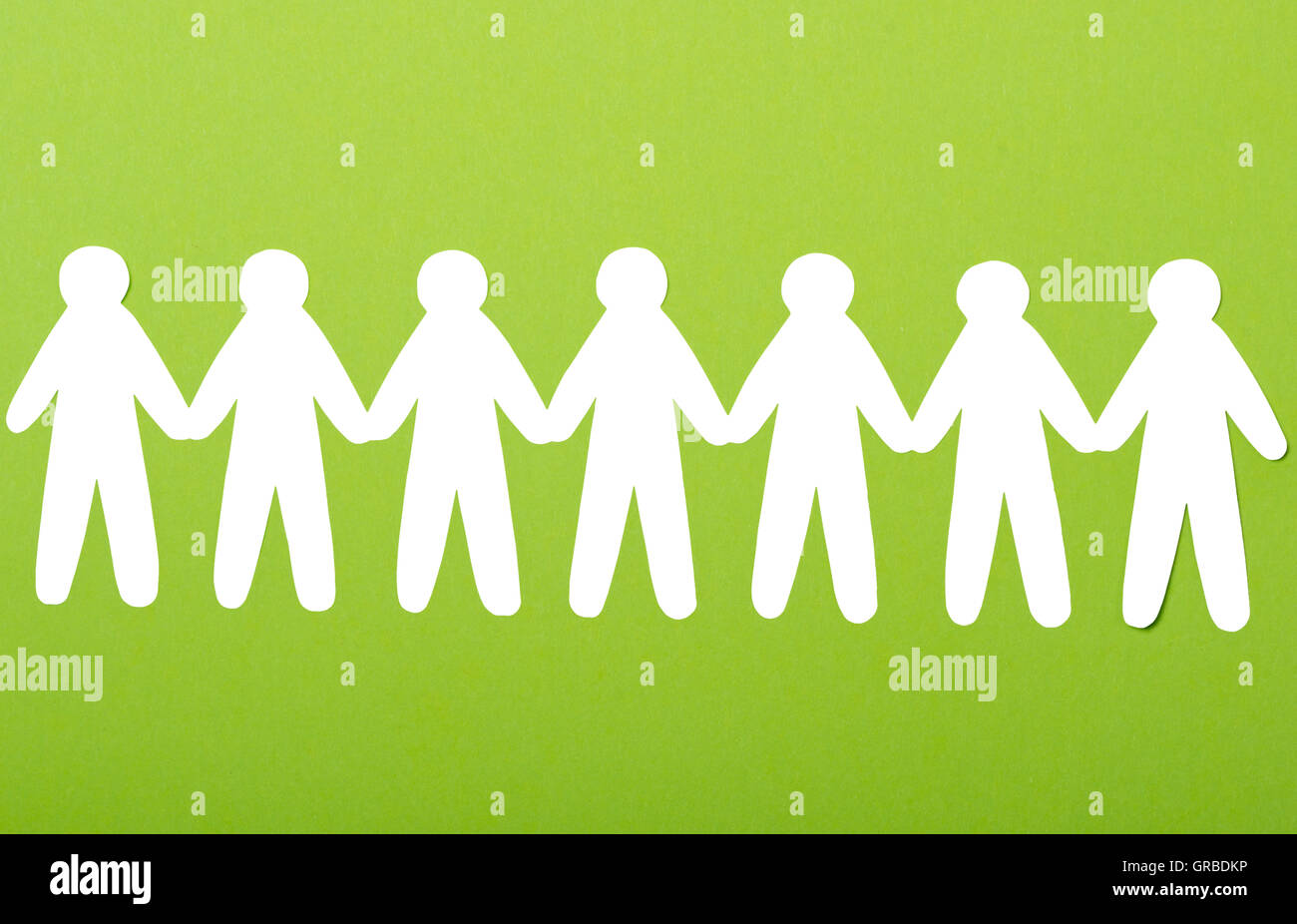 team of paper people on green background - Stock Image