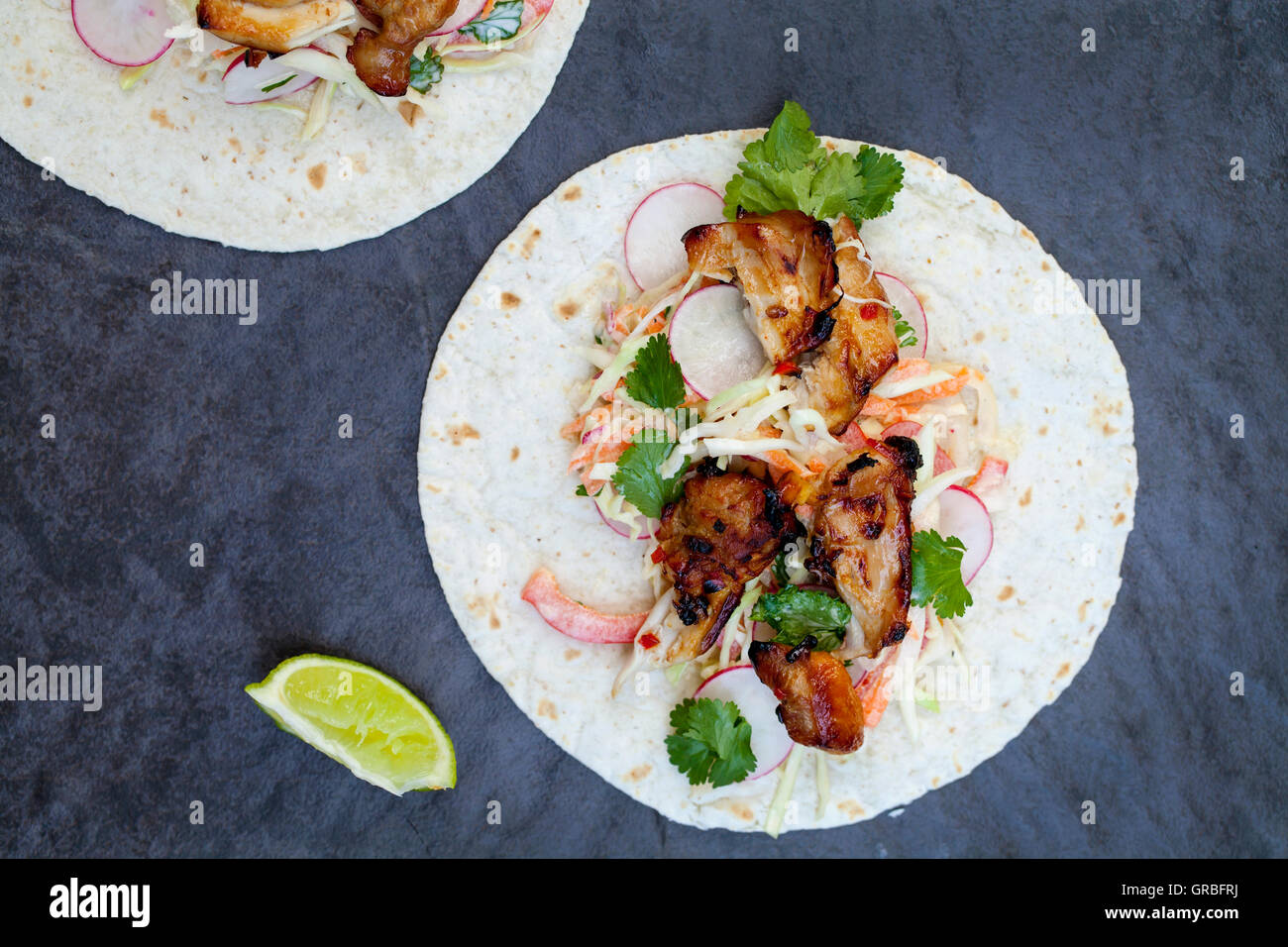 Soft tortillas with spicy chicken tighs - Stock Image