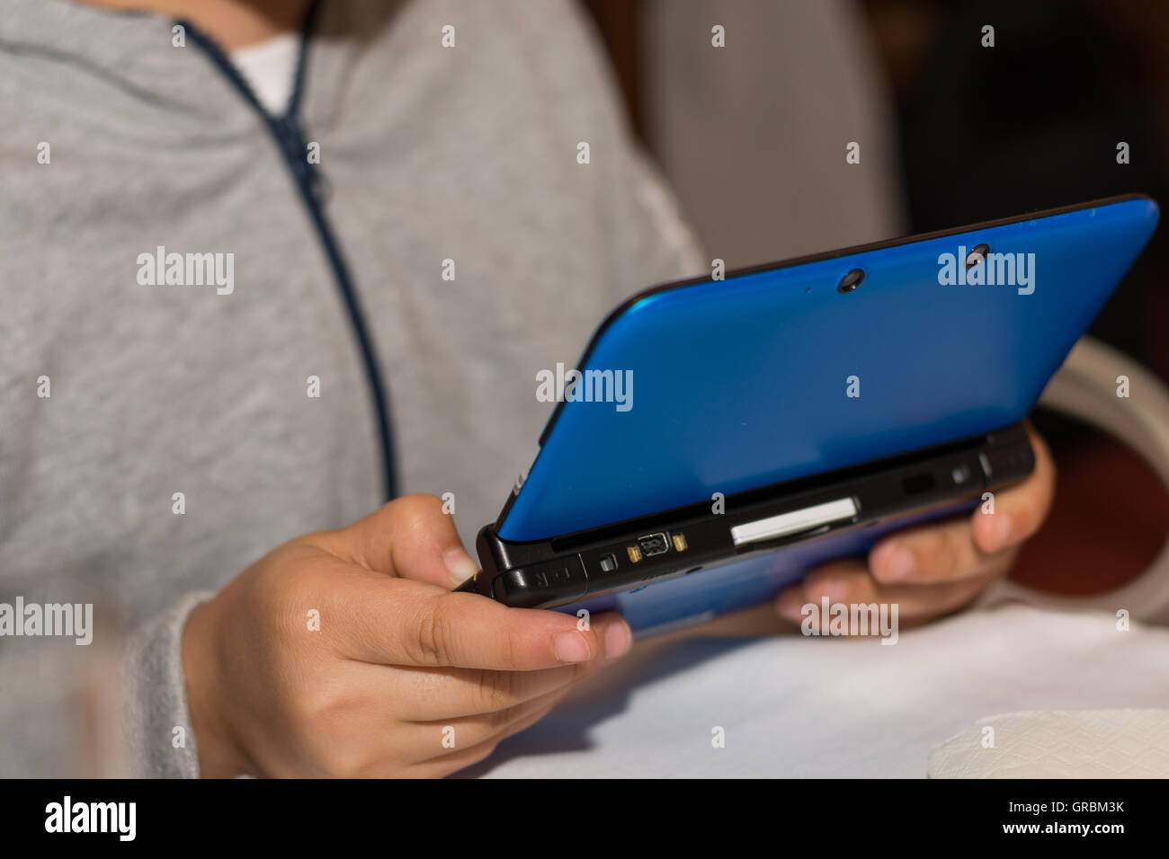 Child Playing On A Portable Computer Games - Stock Image