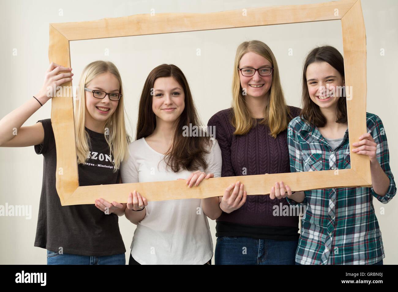 Smiling Girl Quartet With Photo Frames Stock Photo