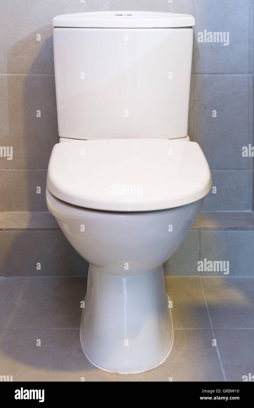A frontal view of a white toilet - Stock Image