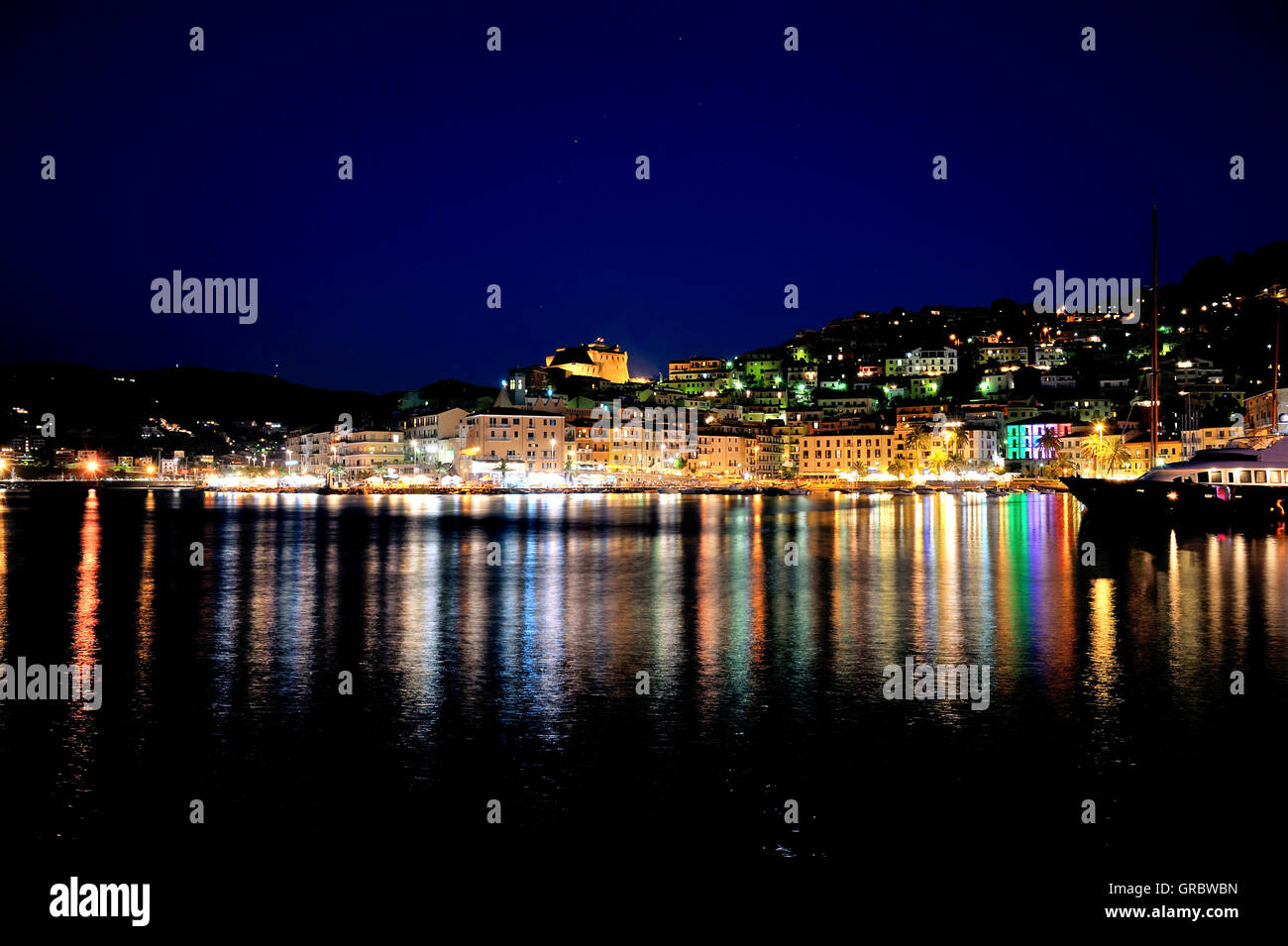 Night Shot Panorama, Colourful Lighting At Night In The Harbour Of Town Porto Santo Stefano, Coast Of Tuscany, Italy - Stock Image