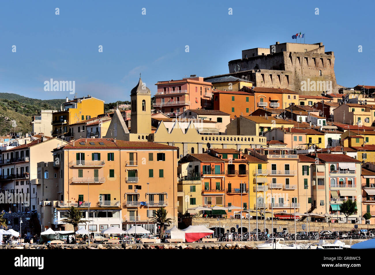 Coloured Houses With Castle And Port Of Town Porto Santo Stefano In Tuscany, Italy - Stock Image