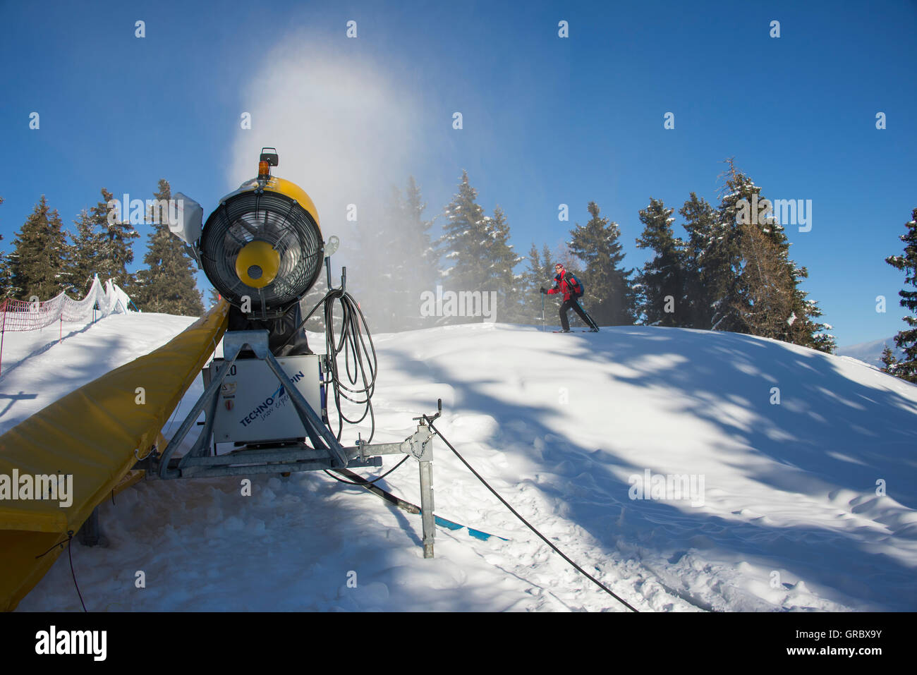 Active Yellow Snow Cannon In Front Of Snowshoer, Fir Trees And Blue Sky - Stock Image