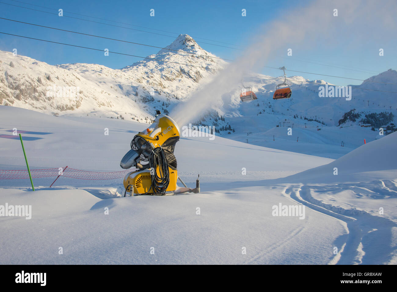Snowfield With Active Yellow Snow Cannon, In The Background Bettmerhorn And Blue Sky - Stock Image