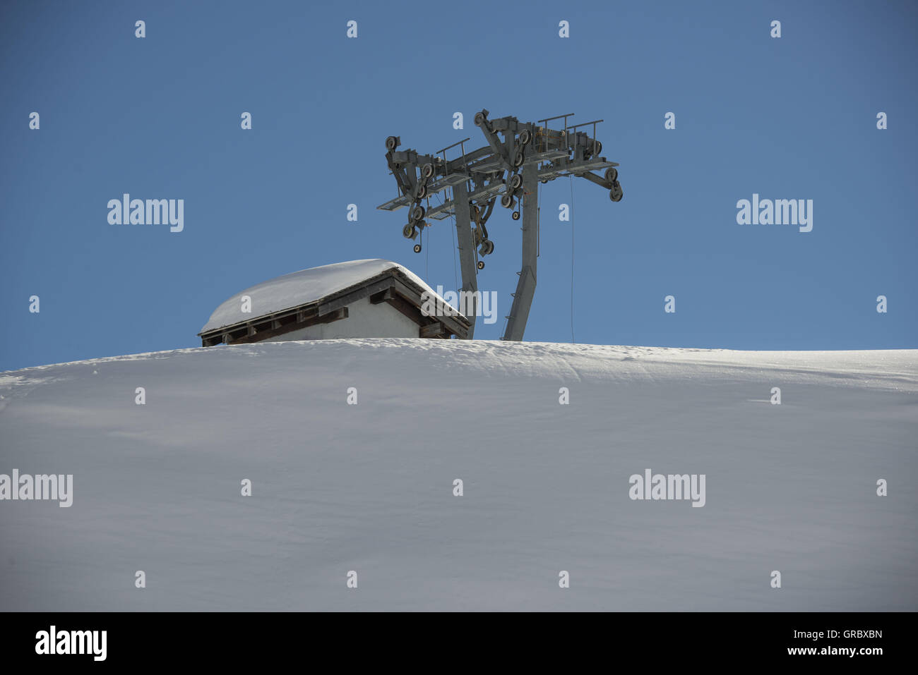 Snowcovered Slope With Old Discarded Skiliftpole, Roof And Blue Sky - Stock Image