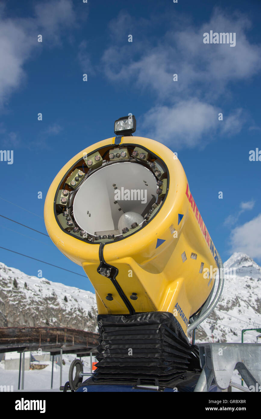 Inactive Yellow Snow Cannon Against Blue Sky, In The Background Snow Covered Mountains - Stock Image
