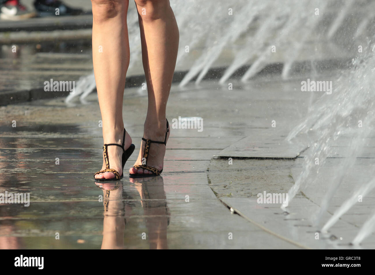 Woman S Legs In A Fountaun During Heat Wave - Stock Image