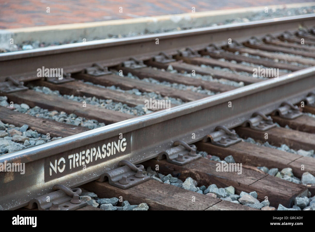 Flagstaff, Arizona - A stenciled 'No Trespassing' sign on the busy BNSF railroad tracks in downtown Flagstaff. - Stock Image