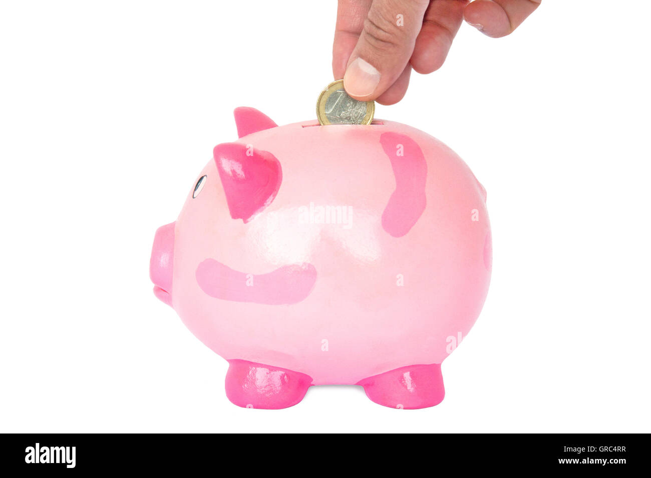 Female Hand Throwing On Euro Into A Pink Piggy Bank - Stock Image