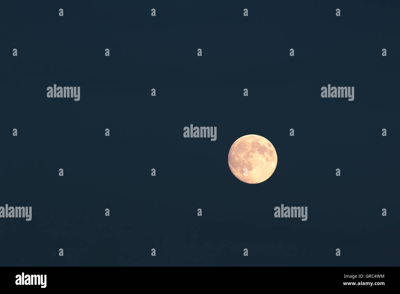 Full Moon Over Dark Blue Night Sky - Stock Image