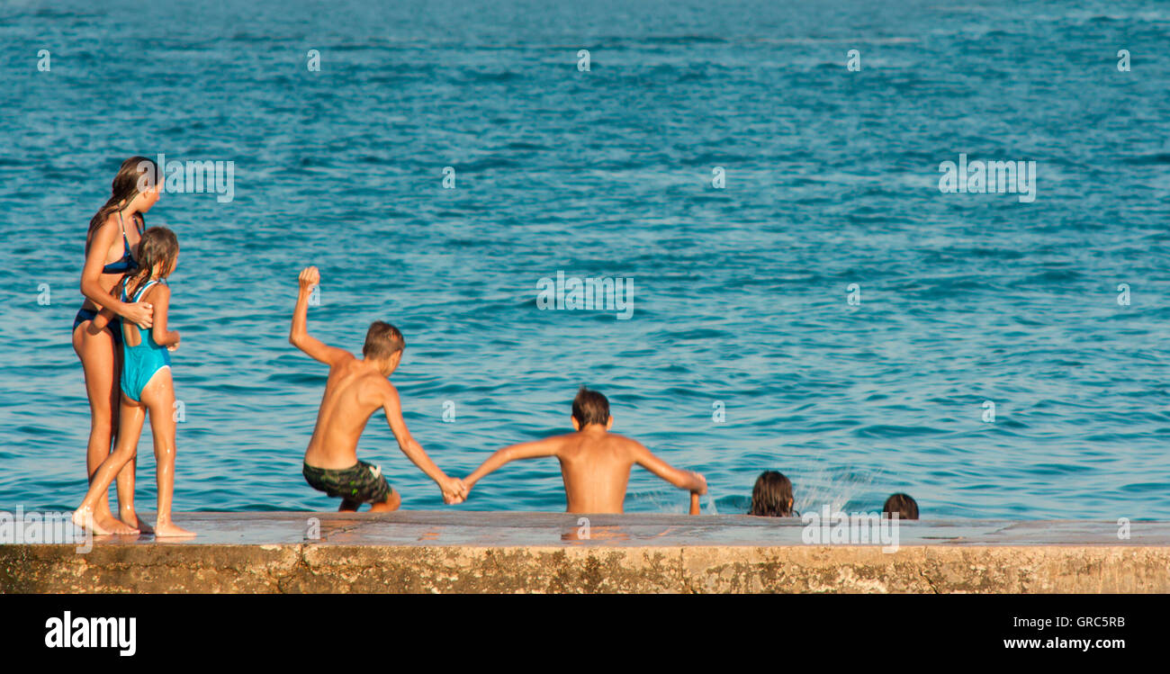 Vodice, Croatia - August 21, 2016: Two young girls watching four pre-adolescent boys holding hands while jumping - Stock Image
