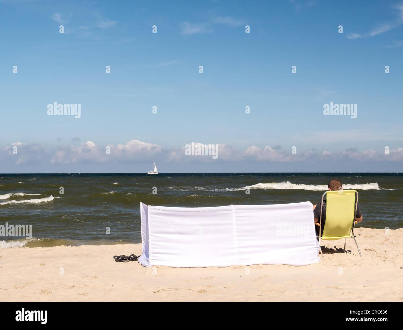 Relaxed sunbather sitting on yellow sunlonger next to white windbreak at the beach - Stock Image