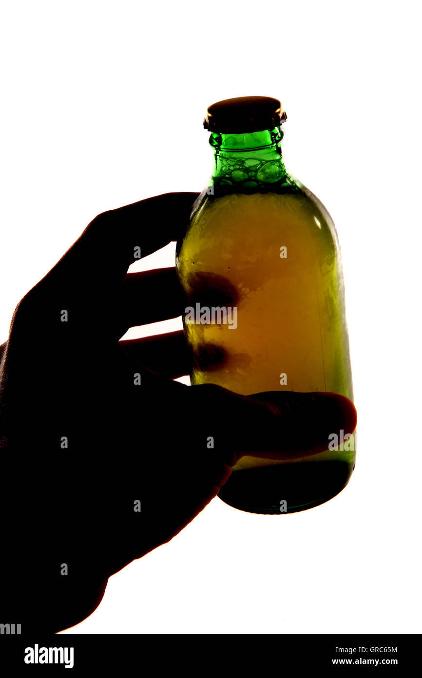 Silhouette of hand holding bottle of larger cutout - Stock Image