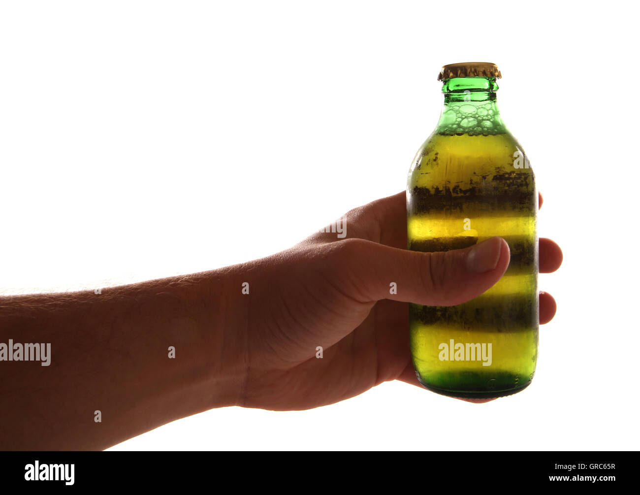 Hand holding a mini bottle of larger cutout - Stock Image