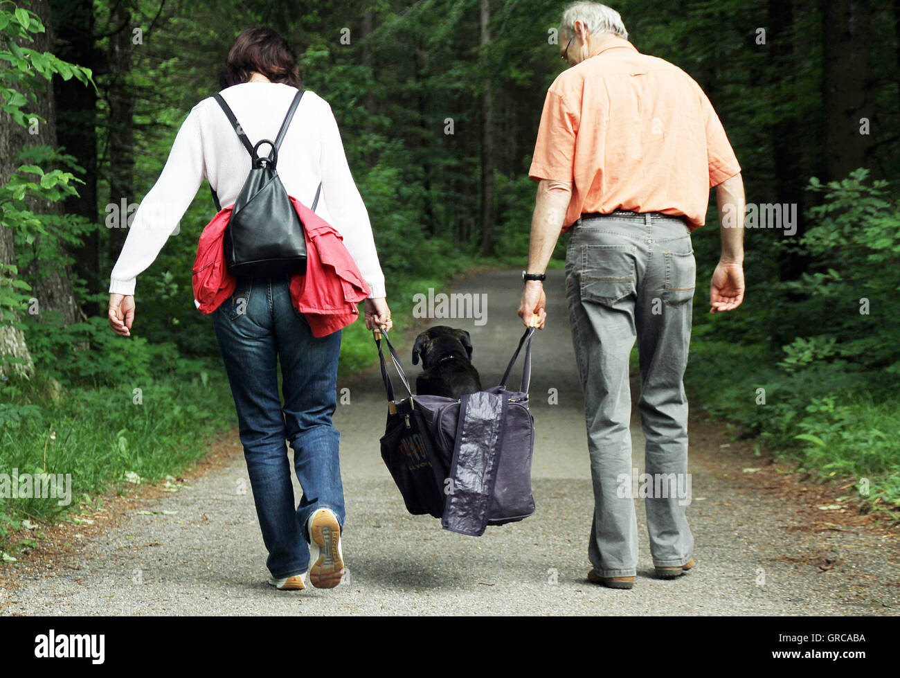 Two Hikers Carry Their Tired And Decrepit Dog In A Bag - Stock Image