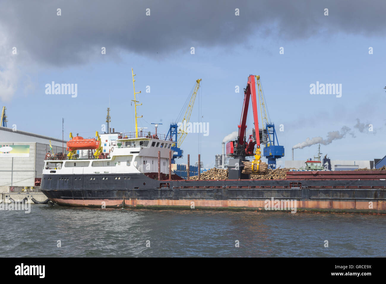 General Cargo Vessel With Timber Is Unloaded At The Port Of Wismar From Excavator - Stock Image