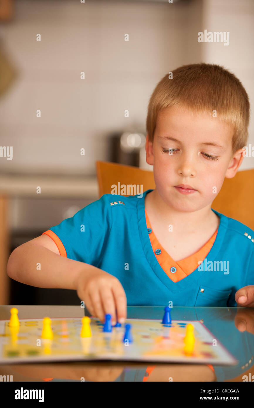 Boy playing ludo game at home. Stock Photo