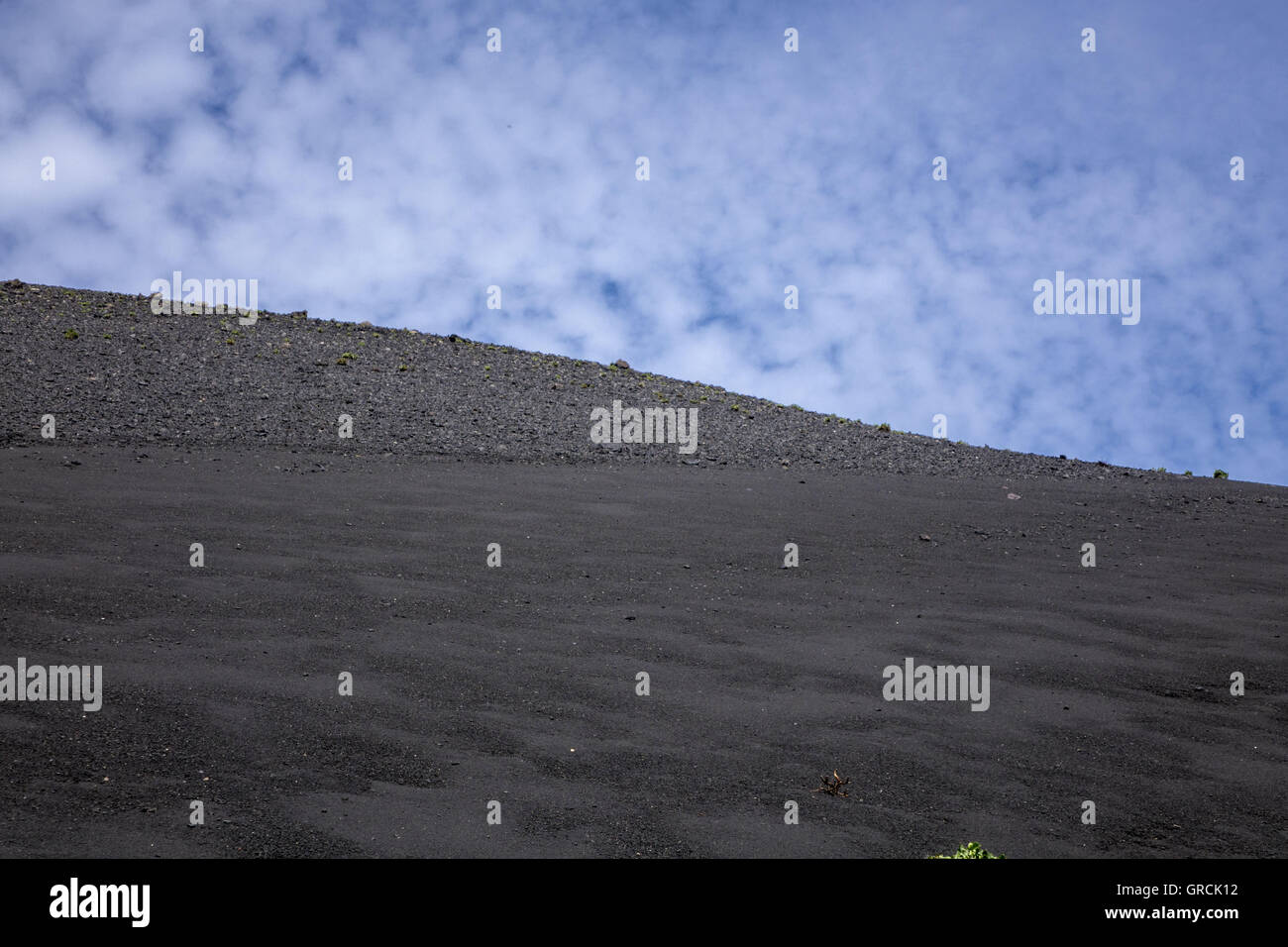 Gentle Slope Of Volcanic Ash, Upper Part Rath Coarse Rock. In The Back Blue Sky With Cotton Wool Clouds. Volcano - Stock Image