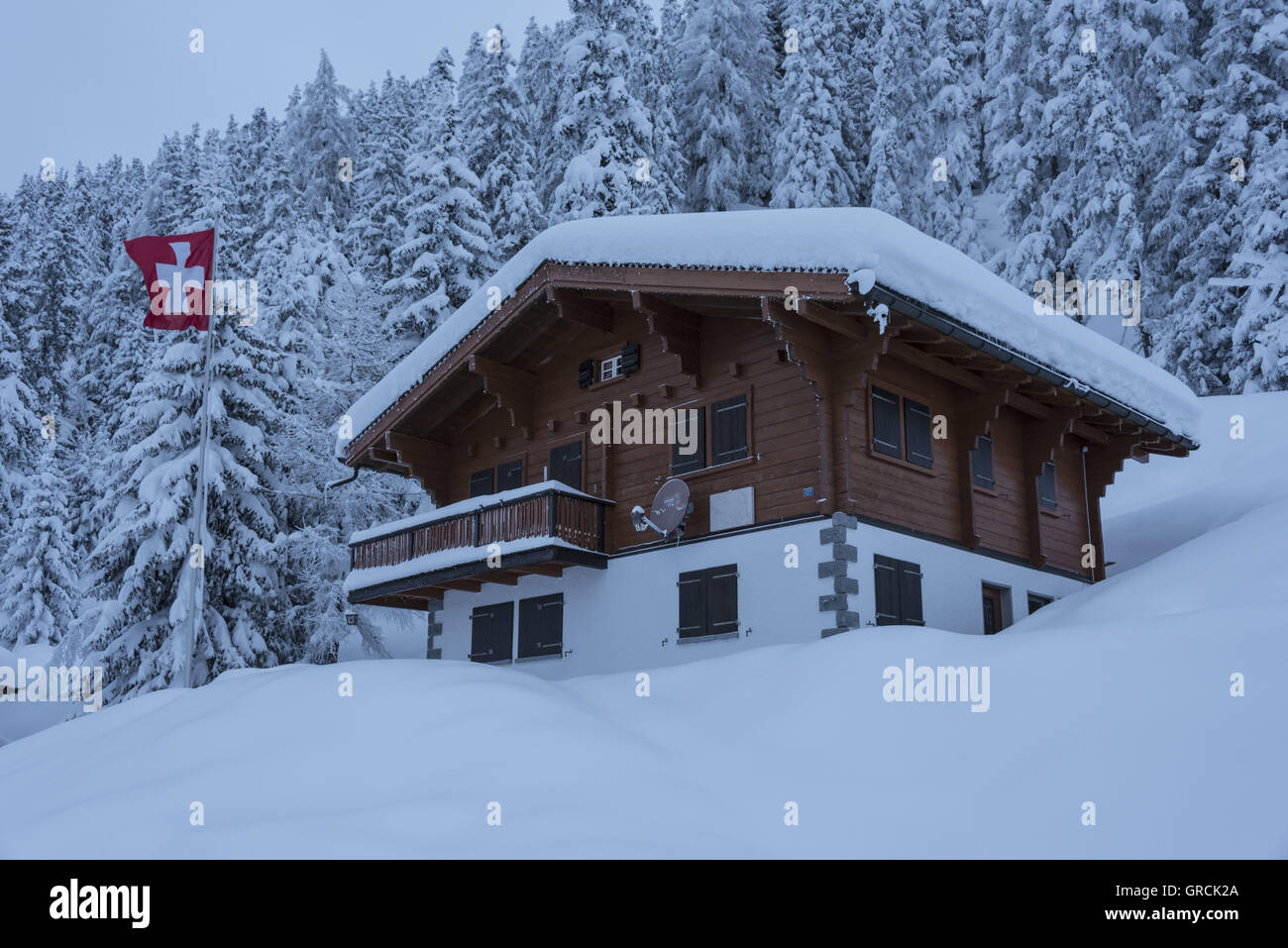 Swiss Chalet In Front Of Deeply Snow Covered Fir Forest With Flag Waving The