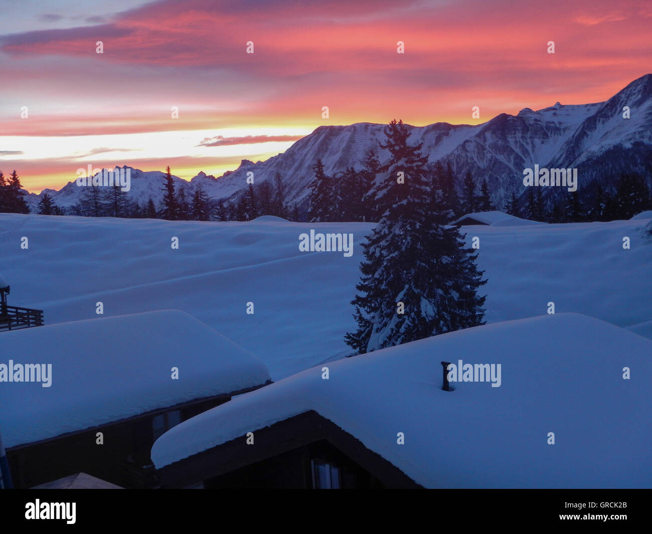 Dawn. View Over Snowcovered Roofs Of Chalets To The Mountains. Sky Orange Pink Colored - Stock Image