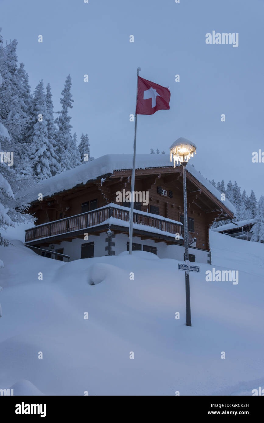 Dawn, Wintry Landscape With Snowcovered Forest, Chalet, Icecled Streetlamp And Waving Swiss Flag. - Stock Image