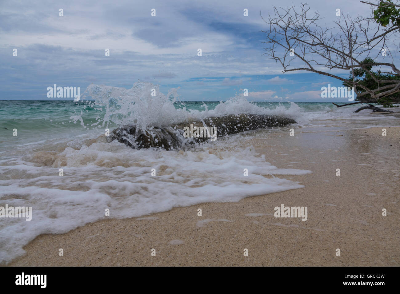 Splashing Waves Rolling On Sandy Beach Stock Photo