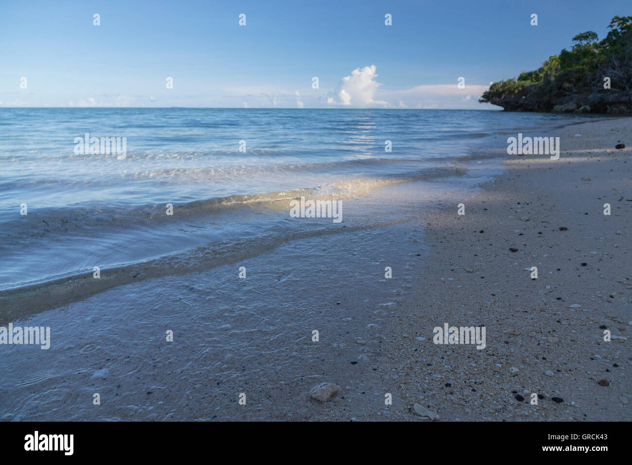 Tiny Waves In Gentle Light Wash Ashore The Sandy Beach Of Selayar - Stock Image