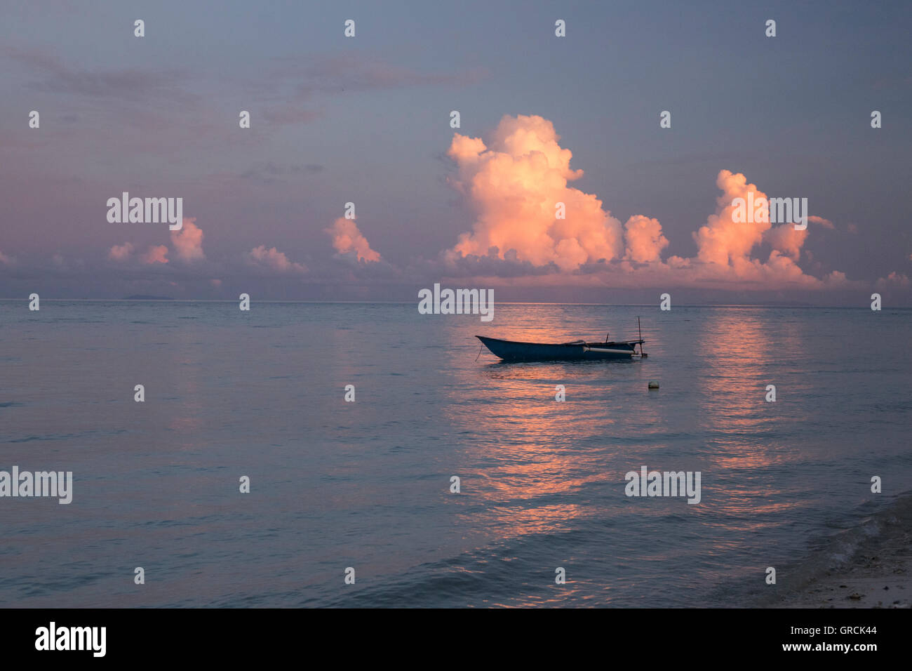 Indonesian Outrigger Canoe On The Sea In Gentle Evening Light, Rosy Cumulus Clouds In The Background - Stock Image