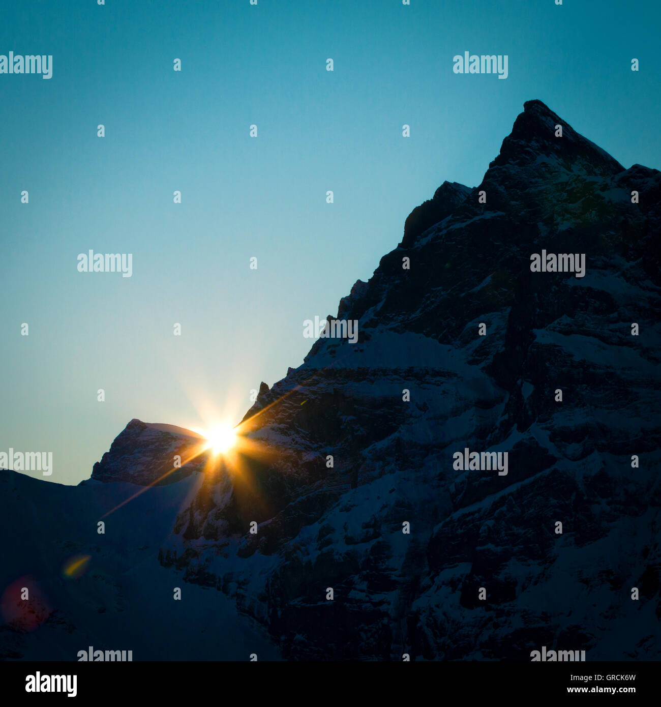 Rising Sun Behind Mountain Silhouette - Stock Image
