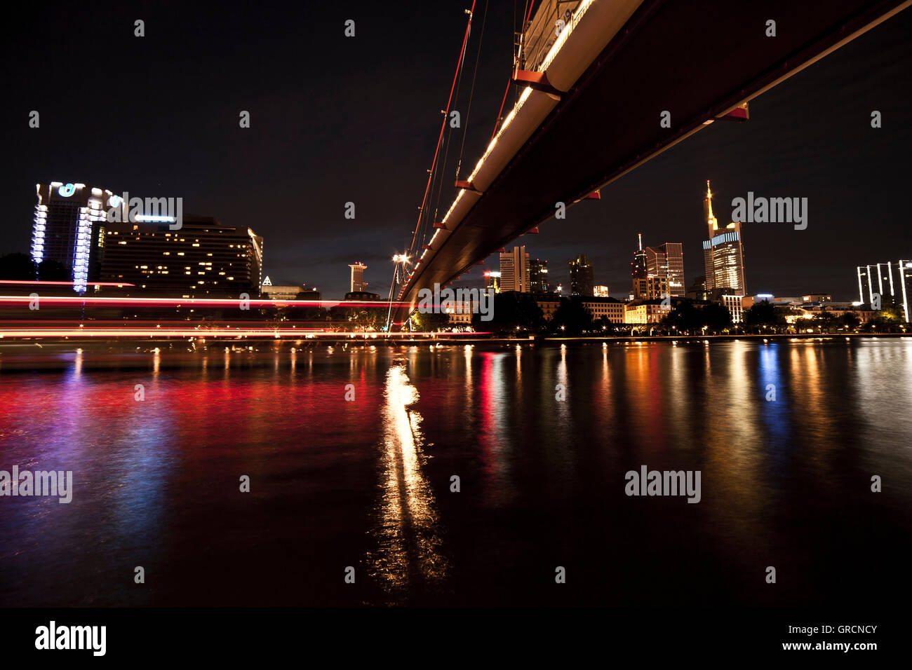 Holbeinbridge In Frankfurt, Shot From Below At Night With Skyline And Moving Lights - Stock Image