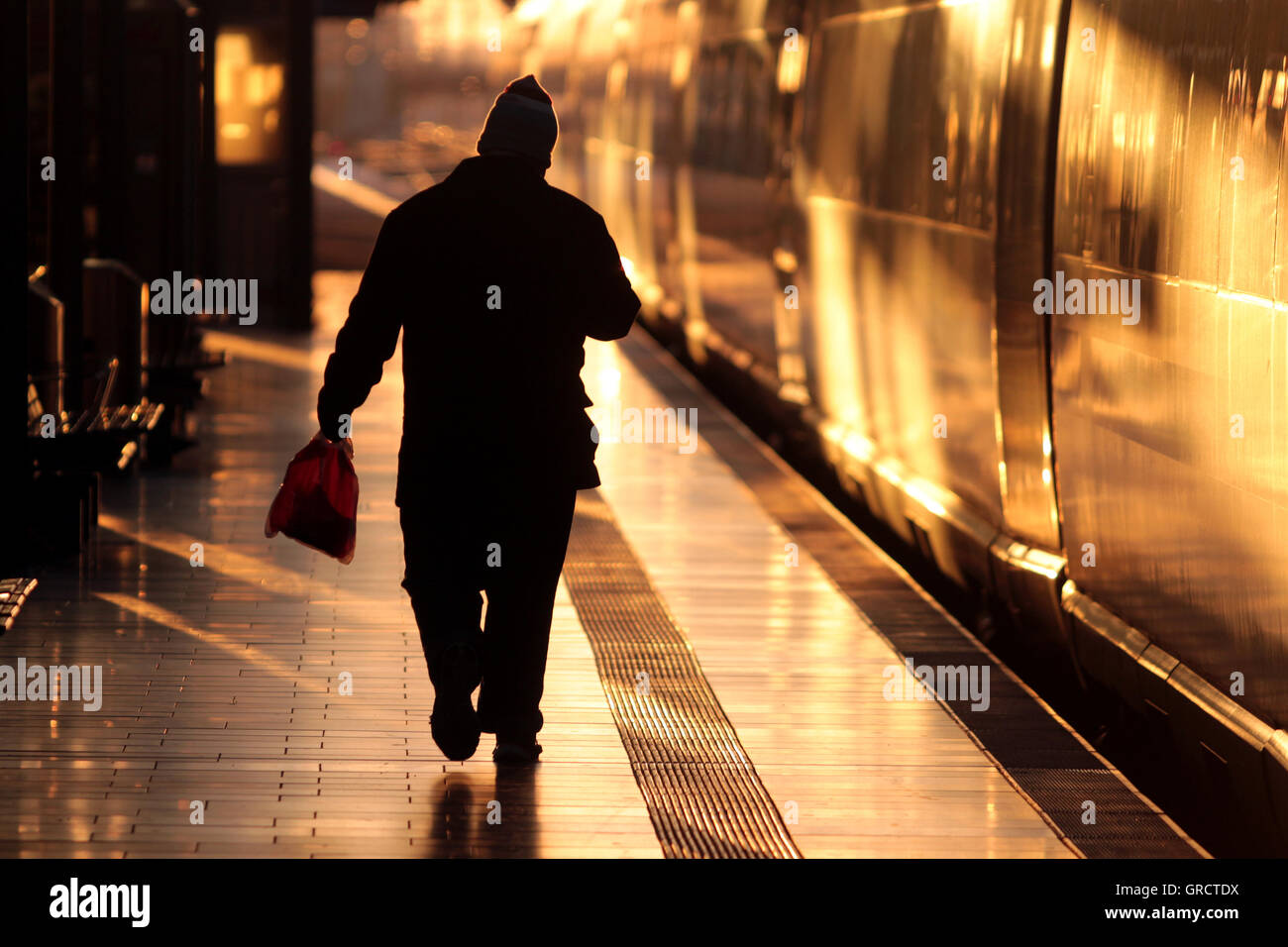 Rail Traveler Walking Down The Platform To A Ice Train During Sunset - Stock Image