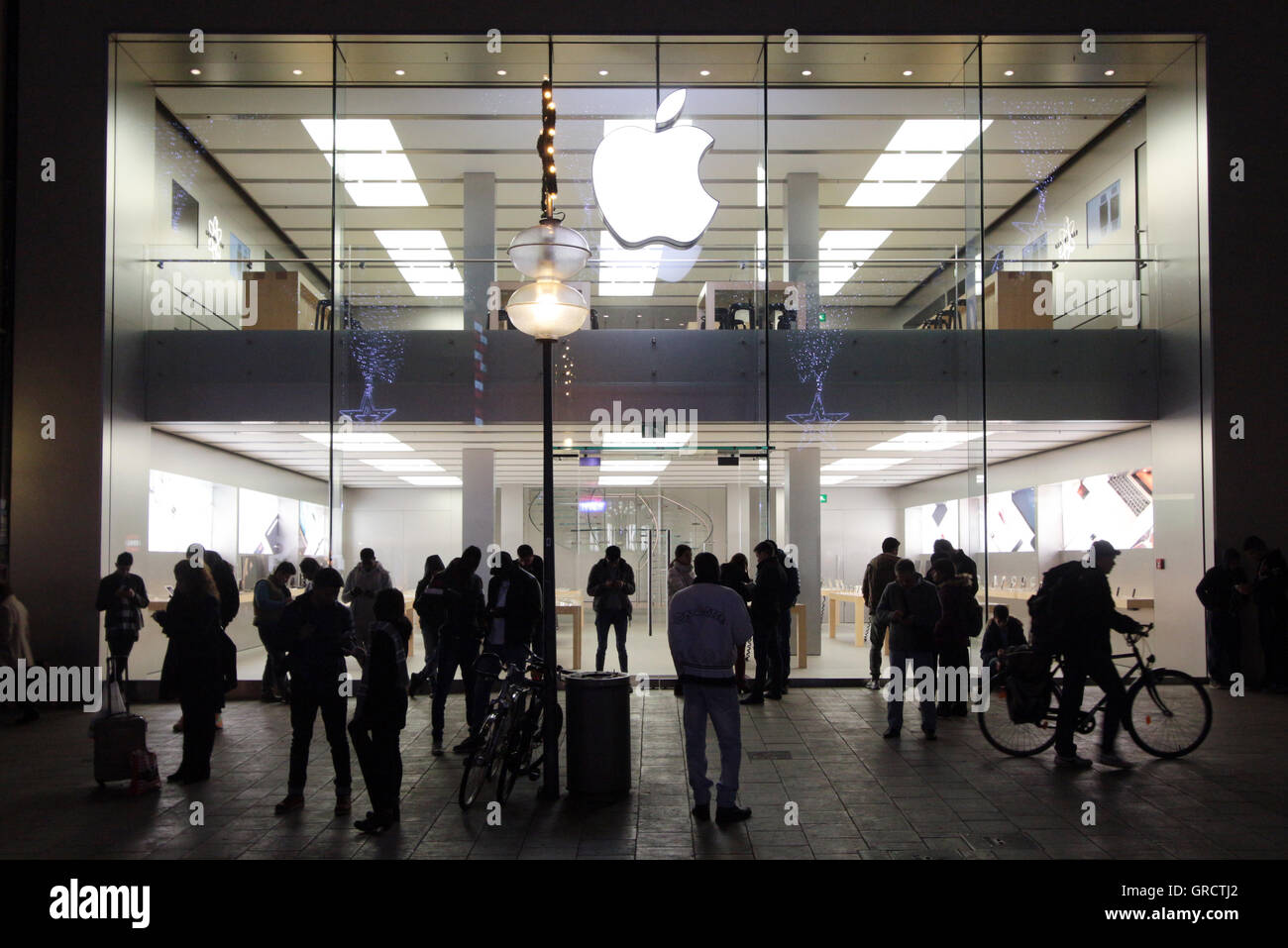 Group Of People Using Hot Spot At A Closed Apple Store In Munich At Night - Stock Image