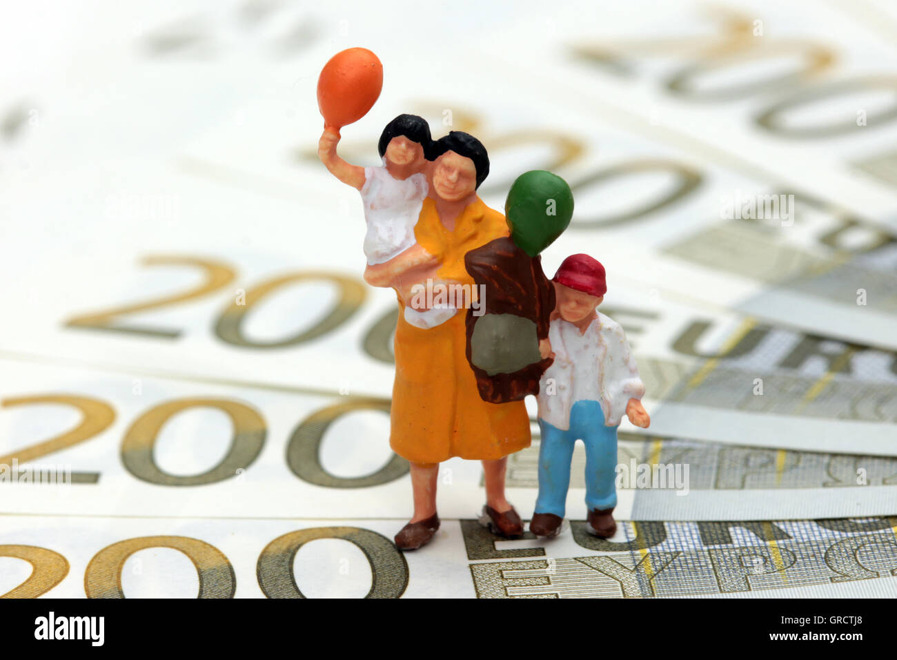 Child Benefits And Allowance Miniature Mother With Kid On Euro Bills - Stock Image