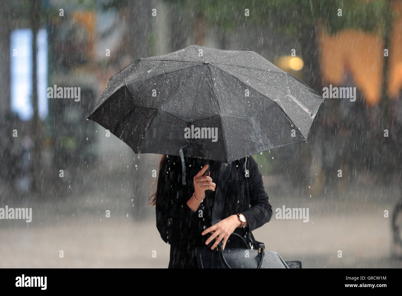 Woman With Umbrella In Heavy Rain - Stock Image