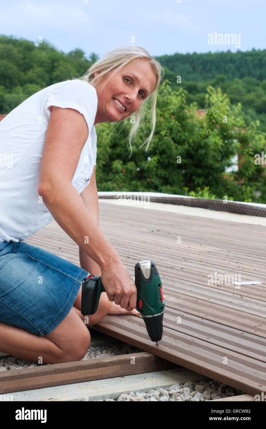 Young Woman With Screwdriver Attaching Wooden Planks On A Terrace Stock Photo