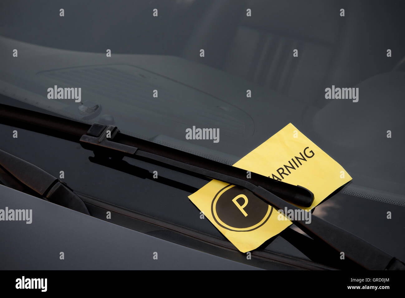 Parking ticket on the windshield of a dark car - Stock Image
