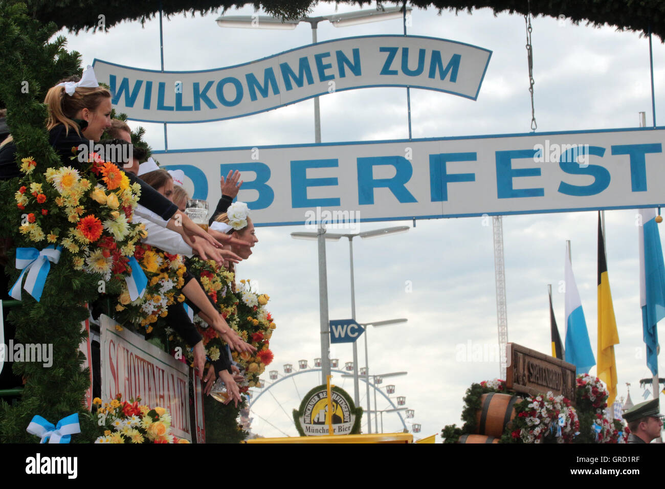 Sign Welcome To Munich Oktoberfest With Partying Guests On Horse Drawn Carriage - Stock Image