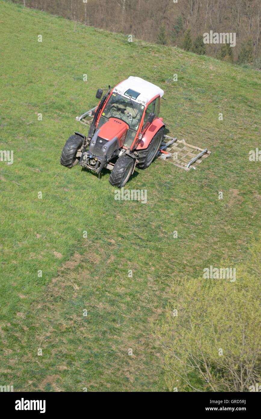 Red Tractor On Mountain Meadow - Stock Image