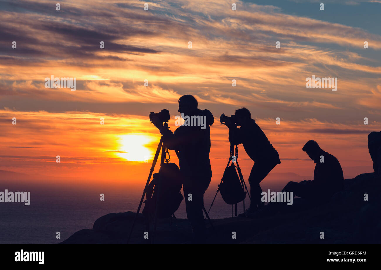 A Group of Photographers on the Cliff Top Taking Sunset Pictures - Stock Image