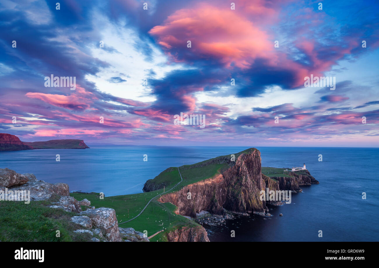 Spectacular Red Sunset Clouds over Neist Point Lighthouse on the Isle of Skye in Scotland Stock Photo