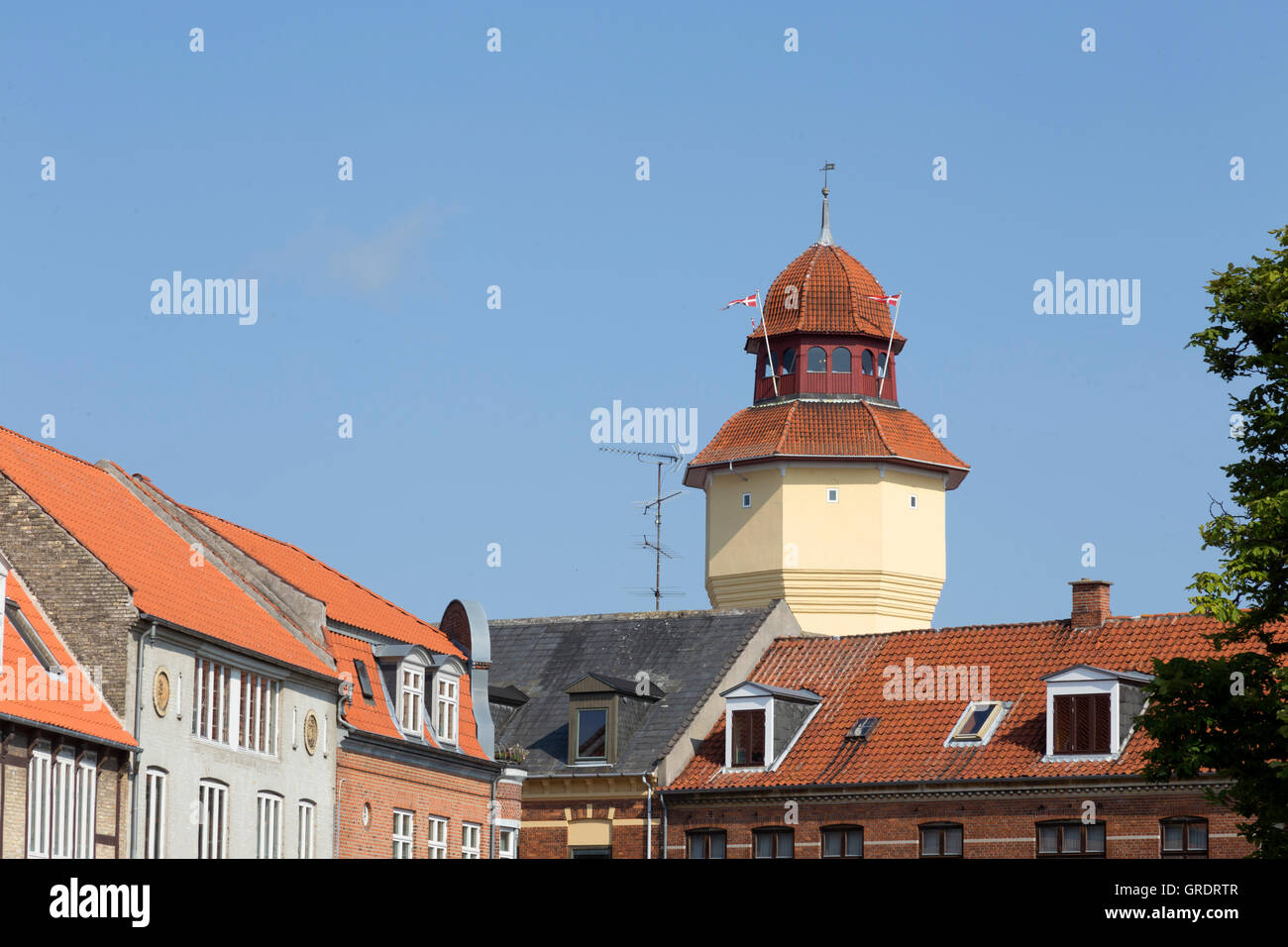 Yellow Painted Former Water Tower Behind Apartment Buildings In Nykobing - Stock Image