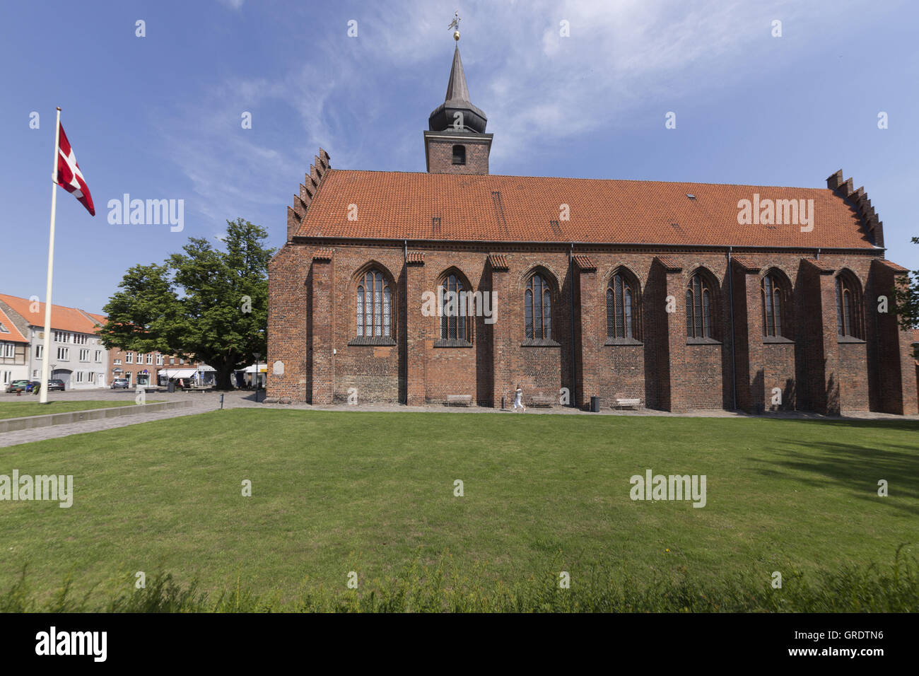 Monastery Church Of Nykobing With Great Grassy Area In Front Of And Next To National Flag - Stock Image