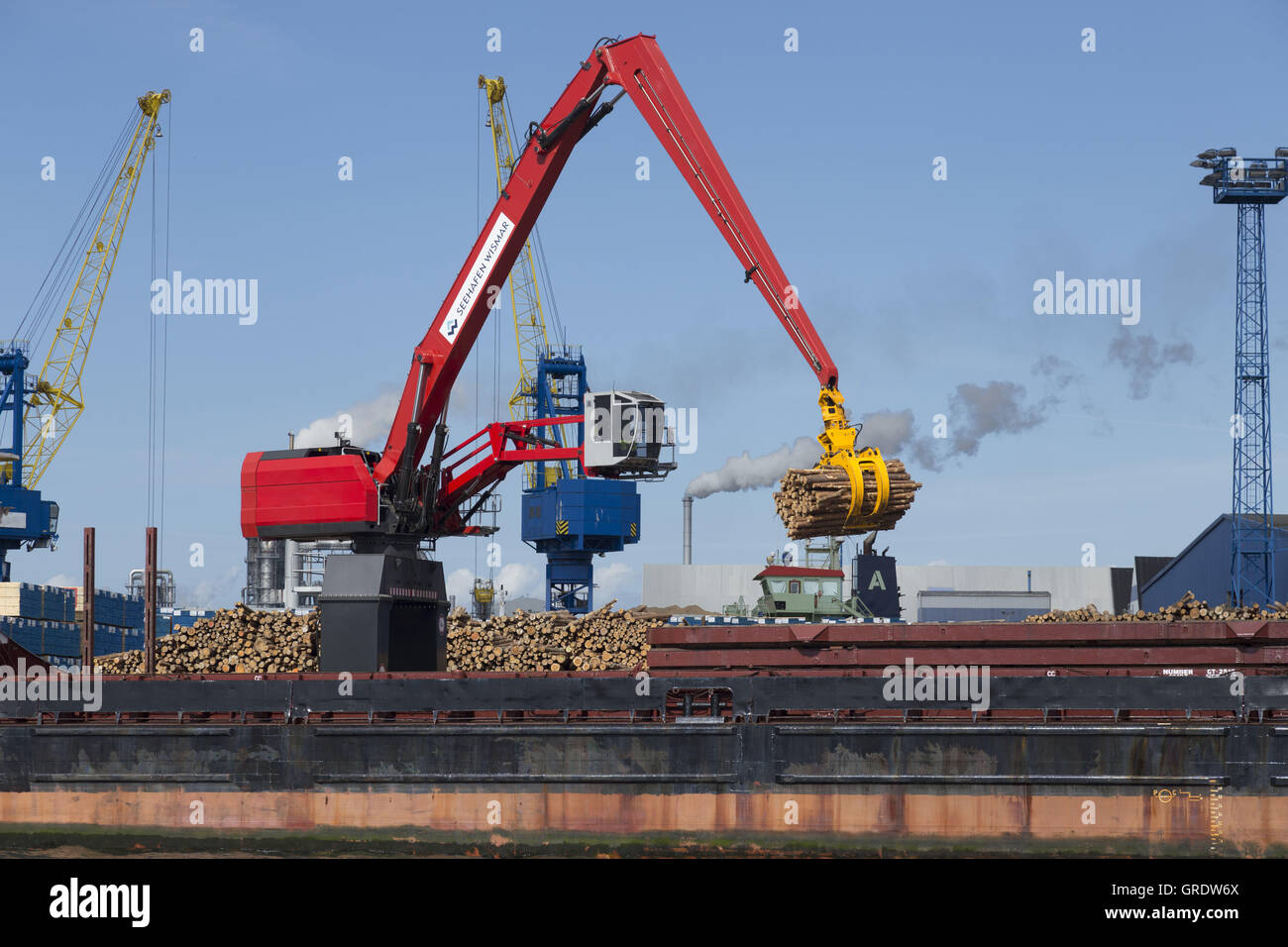 Large Red Excavator Unloads Timber From A Cargo Freighter In Port Of Wismar - Stock Image